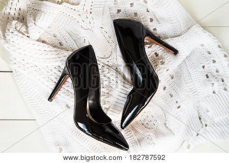 Stylish Black Stiletto Shoes or High Heels on White Knitted Sweater, Flat Lay, Top View