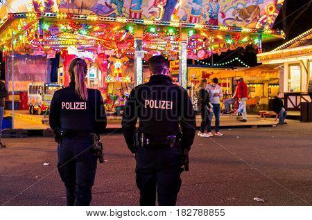Frankfurt am Main, Germany - April 21, 2017: Police officers walking in dippemess in Frankfurt am Main, Germany at night.