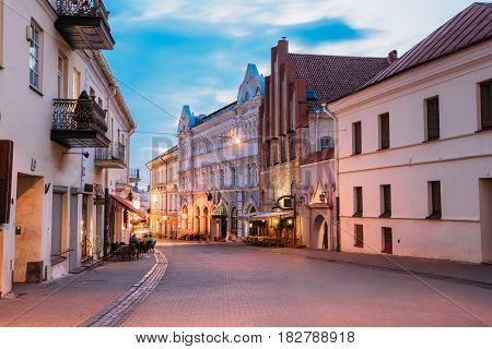 Vilnius, Lithuania. View Of Illuminated Ausros Vartu Street, Famous Showplace Of Old Town With Outdoor Cafe And Ancient Red Brick Building In Summer Twilight Under Blue Sky.