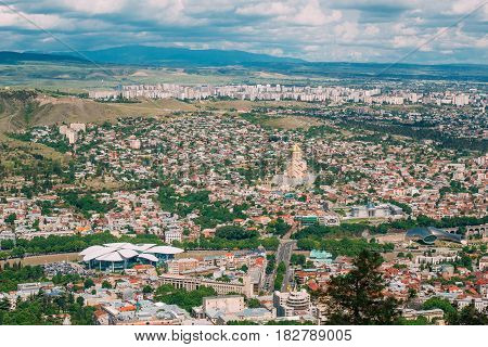 Tbilisi, Georgia. The Aerial Panoramic View Of Georgian Capital With Famous Landmarks: Justice House, Music Theatre And Sameba Holy Trinity Cathedral. Cityscape In Summer Sunny Day Under Blue Cloudy Sky.