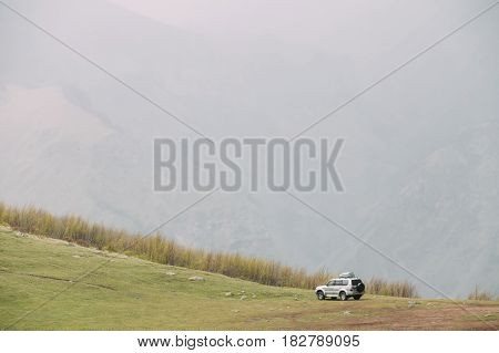 Gray SUV Car On Off Road In Spring Mountains Landscape In Georgia. Drive And Travel Concept. Landscape Of Gorge At Spring Season. Rainy Weather