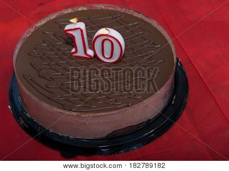 chocolate cake for 10 birthday. on red background with candals