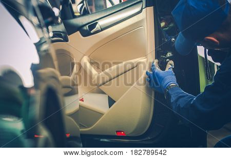 Car Mechanic Trying to Fix Vehicle Door Lock. Automotive Technician Looking at the Central Locking System.