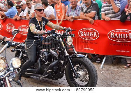 LE MANS FRANCE - JUNE 13 2014:Parade of pilots racing. Old women on motorcycle in Le Mans France.