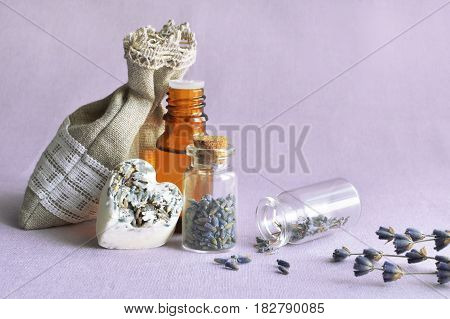 bottle with lavender oil, heart shape soap bar and sachet with dry flowers, aromatherapy spa concept