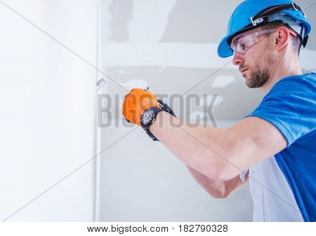 Preparing Electric Installation. Caucasian Electric Technician Installing Electric Outlet Inside the New Apartment.