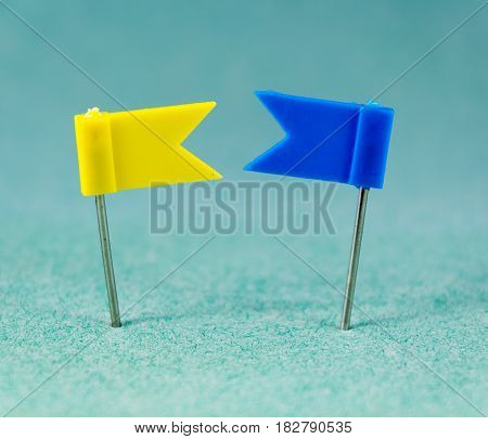Yellow and Blue flag pins on a green background