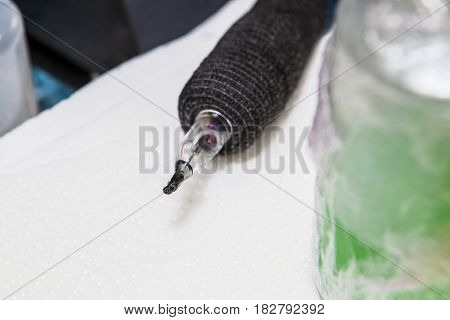 Pen ink machine over paper towel with head covered with black ink. Closeup