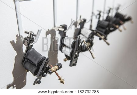 Tattoo coil ink machines hanging from hooks on white wall. Closeup