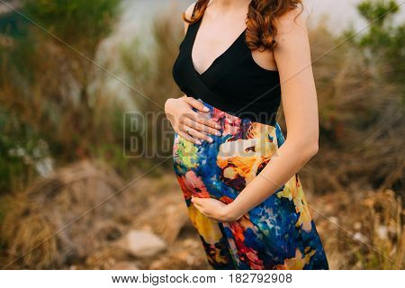 Pregnant woman holding belly with hands in Montenegro