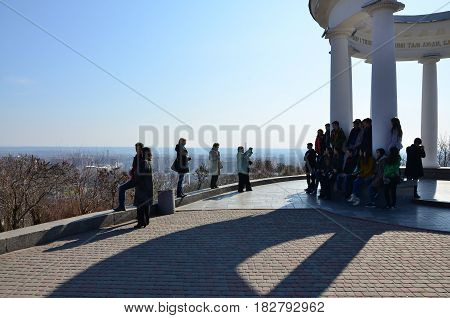 The Guide Makes A Photo To His Group Of Schoolchildren Under The White Rotunda In Poltava