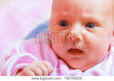 Little newborn baby in pyjamas lying on back. Surprised face expression. Family parenthood childhood concept.
