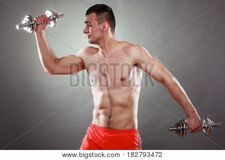 Bodybuilding. Strong fit man exercising with dumbbells. Closeup muscular young guy lifting weights dark background