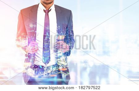 Close up of an African American businessman wearing a suit and a red tie and standing against a night city panorama. Mock up toned image double exposure
