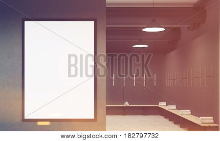Front view of a gray locker room with benches along the rows of lockers. There is a vertical framed poster on a wall. 3d rendering mock up toned image
