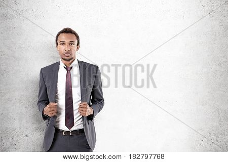 Portrait of a serious African American businessman with a beard wearing a gray suit and a tie standing near a concrete wall. Mock up