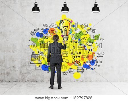 Rear view of a businessman drawing a yellow idea sketch on a concrete wall in a room with three ceiling lamps