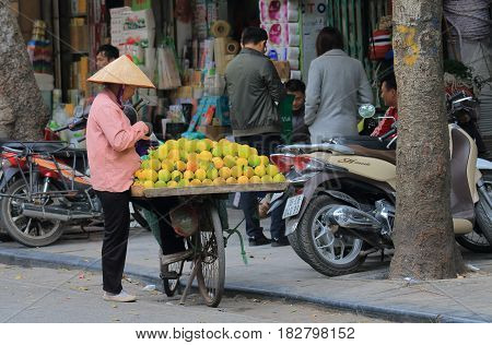 HANOI VIETNAM - NOVEMBER 24, 2016: Unidentified woman sells oranges in Old Quarter.