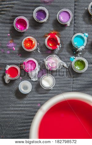 Tattoo artist table with several small cups and plastic glasses. Overhead shot
