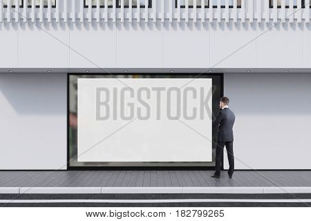 Man looking at a shop window with a large horizontal poster and a white balcony on the second floor. Concept of promotion. 3d rendering mock up
