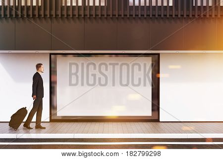 Man with suitcase passing by a shop window with a large horizontal poster and a black balcony on the second floor. Concept of promotion. 3d rendering mock up toned image