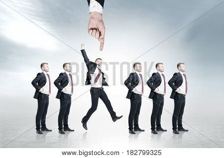 Row of businessmen candidates for a good vacancy is standing against a blurry gray background. A hand is pointing on one of them. He is jumping triumphantly.