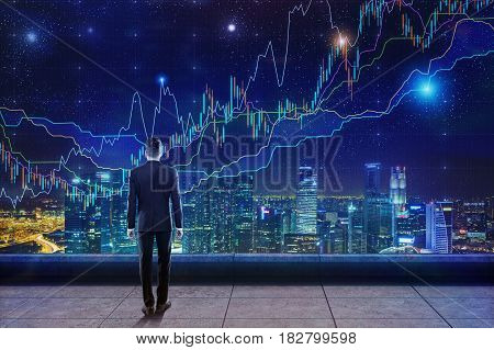Rear view of a busiensssman in a suit standing on the roof and looking at glowing graphs in the night sky