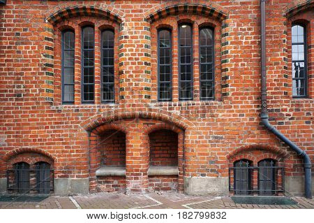 Windows and stone bench in niche of brick wall of Old Town Hall in Hannover, Germany.