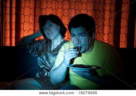 Young Couple Watching A Movie On Tv. The Guy Is Interested, While The Girl Is Bored