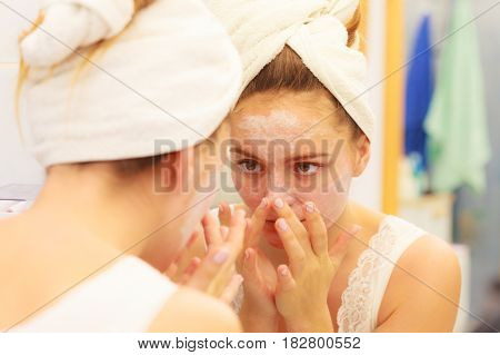 Woman Applying Mask Cream On Face In Bathroom