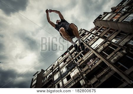 young man doing parkour in  ithe city  summer day