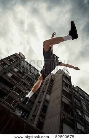 young man doing parkour jump in the city   spring  day