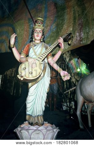 GOMBAK, SELANGOR / MALAYSIA - CIRCA 1990: A Hindu sculpture, of a four-armed woman playing a stringed musical instrument, stands inside the Batu Cave Temples dedicated to Lord Murugan.
