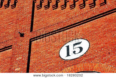 Exterior brick wall with pattern and the number 15 painted in black within a white oval. poster