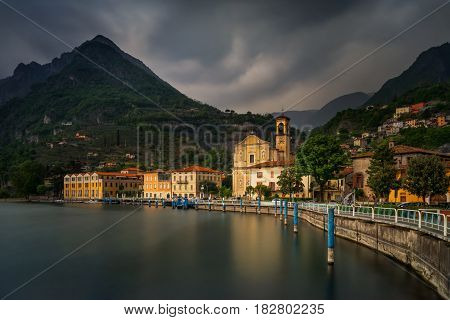 Marone harbour on Iseo Lake with mountains in storm in background Italy