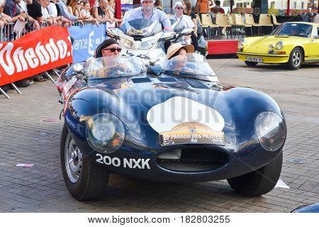 LE MANS FRANCE - JUNE 13 2014: Jaguar at a parade of pilots racing. The pilot is driving a retro automobile