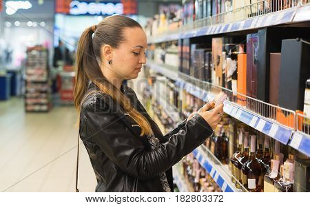 Woman deciding what wine or alcohol to buy. shopping in supermarket concept