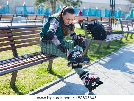 Beautiful young roller girl unscrewing wheels on freeskate roller Skates with Allen key or Hex key tool. Maintenance of professional skates