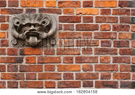 Ancient sculpture of devil on brick wall of Old Town Hall in Hannover, Germany.