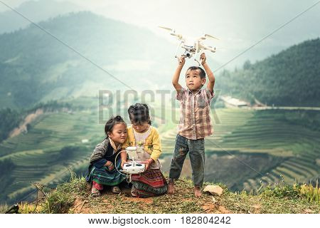 MU CANG CHAI VIETNAM - SEP 22 2016 : Child operating drone flying or hovering by remote control in countryside of Vietnam
