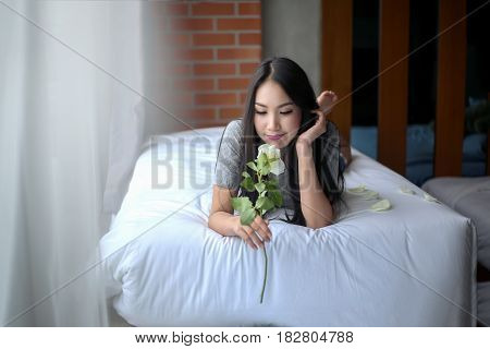Woman smiling daydreaming and relaxing in Bed with rose