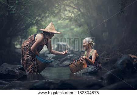 Old Asian woman working in creek, countryside of Thailand