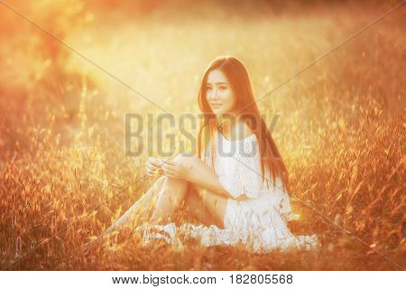 Beauty Romantic Girl Outdoors. Beautiful Teenage Model girl Dressed in Casual Short Dress on the Field in Sun Light. Autumn. Glow Sun Sunshine. Backlit. Toned in warm colors
