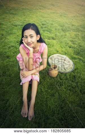 Thai local woman sitting on grass field Thailand