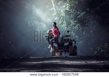 Elegant woman riding quadricycles ATV in forest