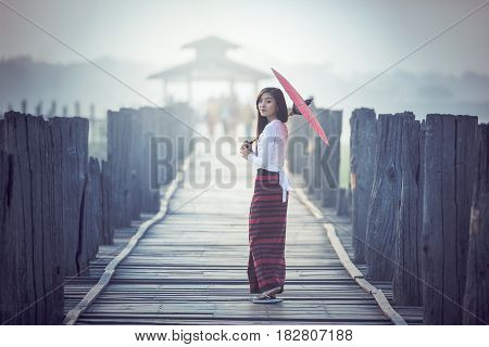 Burmese woman holding traditional red umbrella and walking on U Bein Bridge Myanmar
