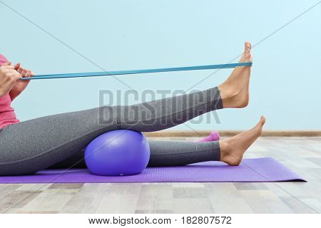 Woman training with elastic band in gym