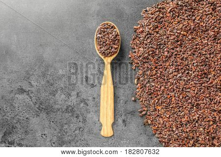 Aromatic cocoa nibs and spoon on gray background