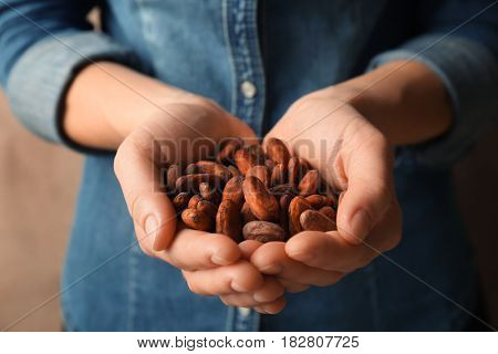 Female hands holding aromatic cocoa beans, closeup