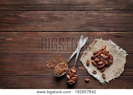 Spoons with aromatic cocoa beans and powder on wooden table